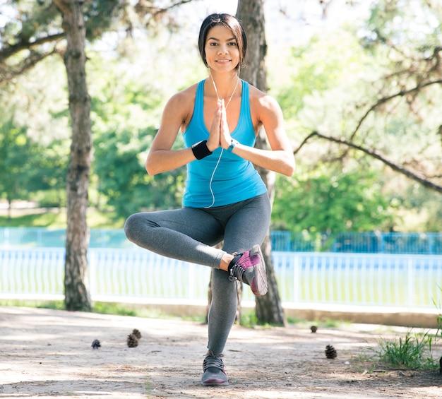 Gelukkig sportieve vrouw die yoga-oefeningen doet