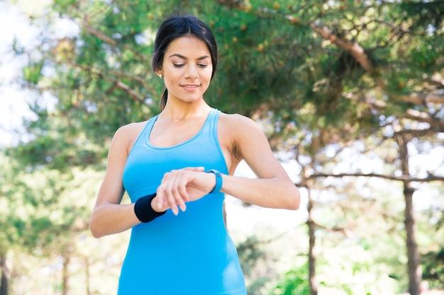 Gelukkig sportieve vrouw met behulp van slimme horloge