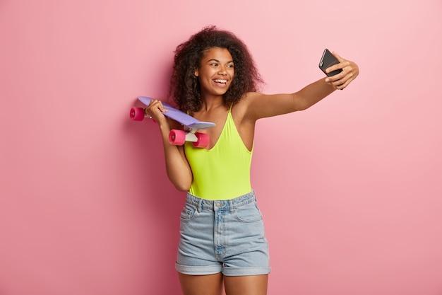 Gelukkig sportieve vrouw poseren met skateboard