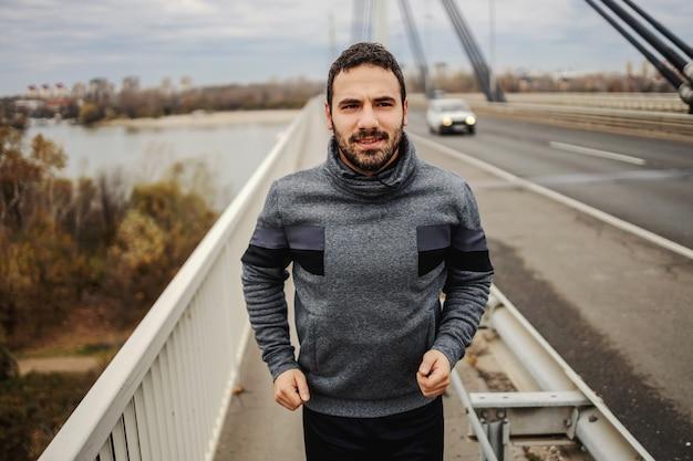 Gelukkig sportman draait op de brug bij bewolkt weer. gezond levensstijlconcept.