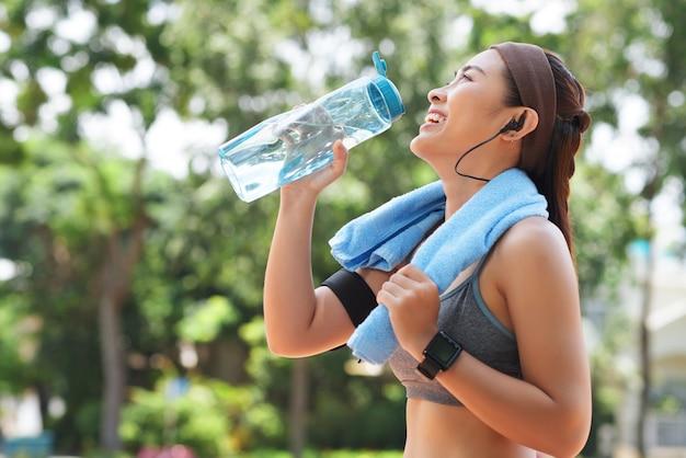 Gelukkig sportvrouw drinkwater in park