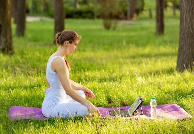 Gelukkig sportvrouw oefenen en kijken naar online oefening op laptop.