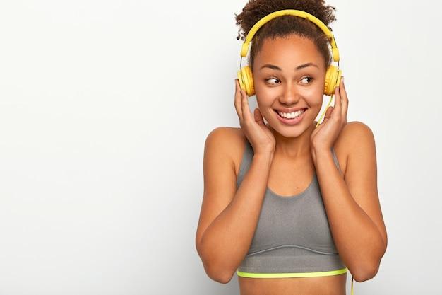 Gelukkig sportvrouw voelt plezier tijdens de training, luistert naar muziekafspeellijst via koptelefoon, gekleed in sportbeha, lacht positief