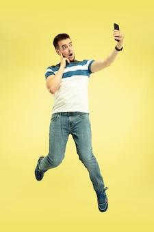 Gelukkig springende jonge man met smartphone op geel.