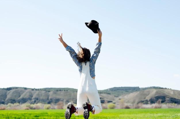 Gelukkig springende vrouw in het veld met hoed in de hand