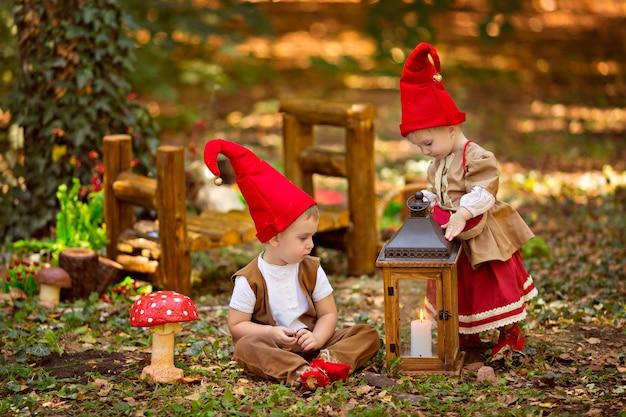 Gelukkig sprookjesachtig baby gnome meisje en jongen spelen in het bos