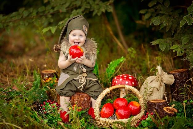 Gelukkig sprookjesbaby kabouterjongen spelen en wandelen in het bos appels eten