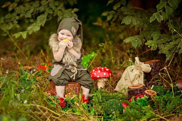 Gelukkig sprookjesbaby kabouterjongen spelen en wandelen in het bos, paddestoelen plukken, appels eten