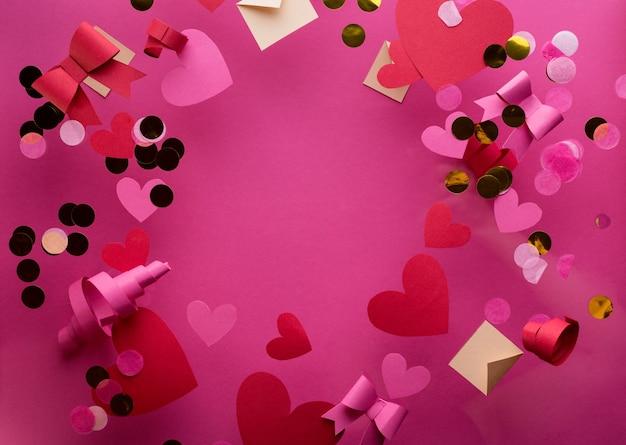 Gelukkig st. valentijnsdag concept met veel rommelige decoratieve rode papieren harten, confetti, strikken tegen roze achtergrond.