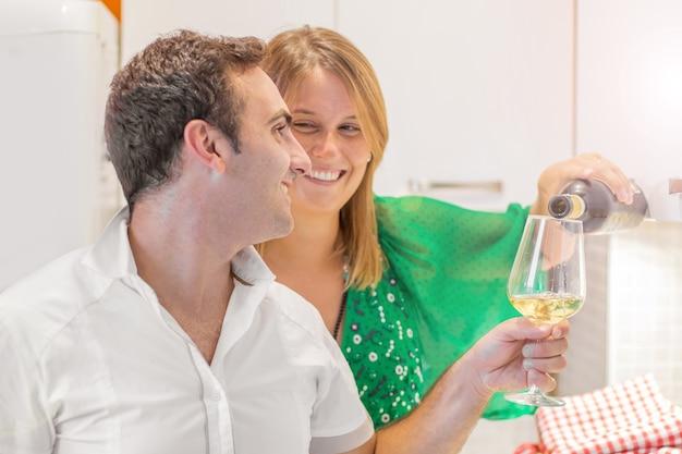 Gelukkig stel drinkt een glas witte wijn in de keuken
