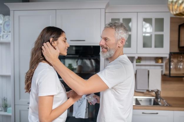 Gelukkig stel. een grijsharige man die zijn mooie jonge vrouw knuffelt