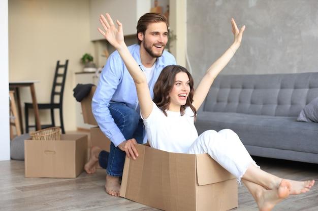 Gelukkig stel heeft plezier met kartonnen dozen in het nieuwe huis op de verhuisdag, een vrouw die in een kartonnen doos zit terwijl de man erop duwt.