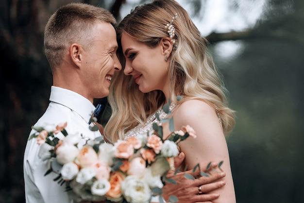Gelukkig stel. jonge mooie bruid en bruidegom met een bruiloft boeket