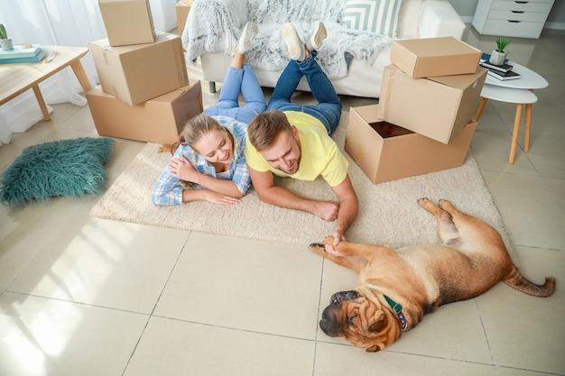 Gelukkig stel met schattige hond na verhuizing naar nieuw huis