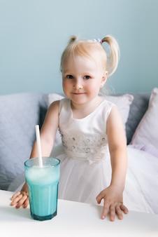 Gelukkig stijlvol babymeisje in een kindercafé drinken van een milkshake
