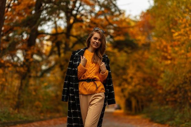 Gelukkig stijlvol jong meisje met mooie glimlach in vintage herfstcollectie kleding met gebreide trui, zwarte jas loopt buiten met oranje bladeren