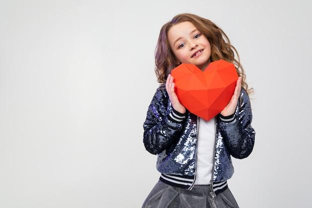 Gelukkig stijlvol kaukasisch meisje met een rood papier hart op een witte muur met lege ruimte