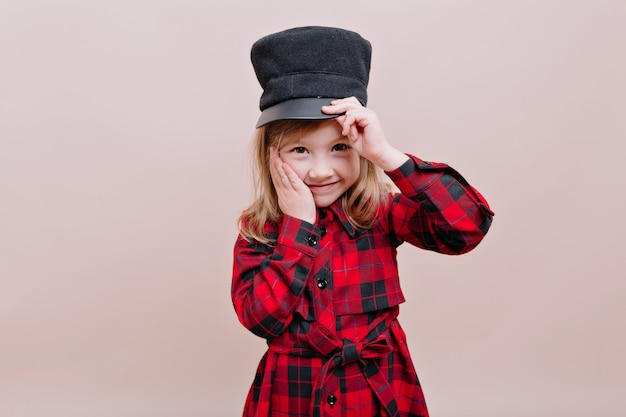 Gelukkig stijlvol meisje draagt zwarte pet en geruit overhemd houdt een pet en haar wang met mooie glimlach