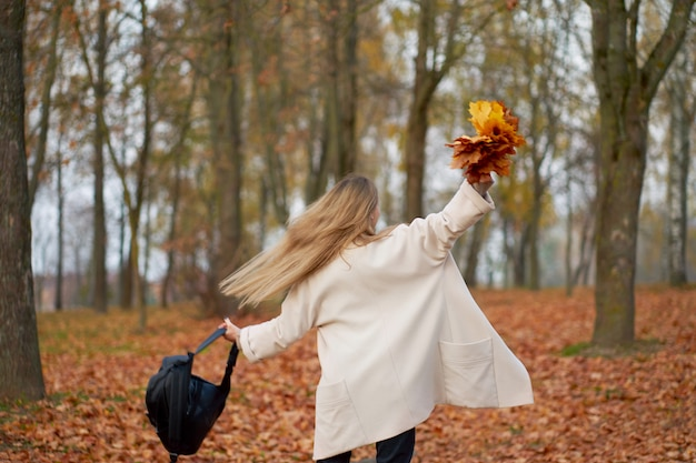 Gelukkig stijlvol meisje trendy herfst jas, zwarte moeder jeans en lederen zwarte rugzak bedrijf boeket herfstbladeren en veel plezier in het herfst park. uitzicht vanaf de achterkant.