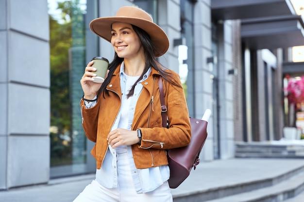 Gelukkig stijlvolle jonge dame met hoed en kopje koffie in de stad te houden. lifestyle-concept