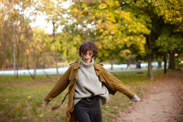 Gelukkig stijlvolle jonge vrij kortharige brunette vrouw spinnen met opgeheven handen en vrolijk lachen terwijl poseren over stadstuin op heldere herfstdag
