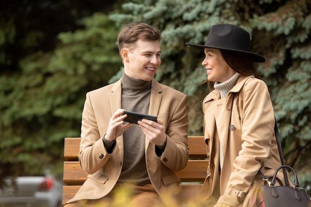 Gelukkig stijlvolle jongeman met smartphone en zijn vriendin zittend op een bankje door naaldboom in park en chatten tijdens chill
