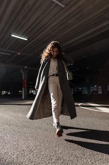 Gelukkig stijlvolle mooie vrouw met krullend haar en een schattige glimlach in een mode lange jas met een handtas loopt op straat. vrouwelijke casual stedelijke stijl en schoonheid