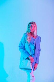 Gelukkig stijlvolle vrouw in modieuze pak outfit met tas met pastelkleurige neon roze lichten in studio