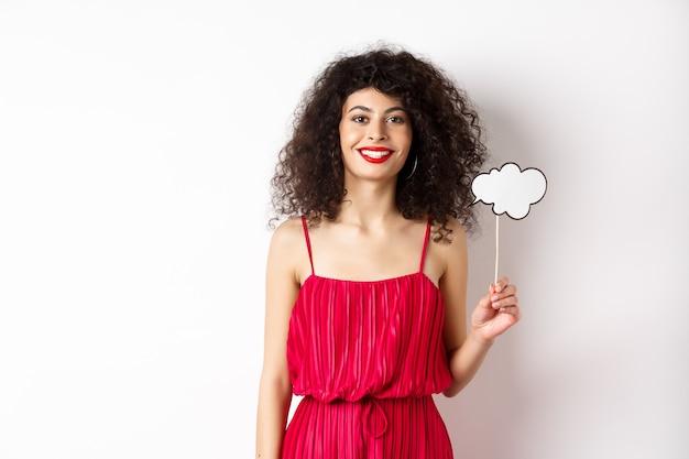 Gelukkig stijlvolle vrouw met krullend haar, beauty make-up, commentaar wolk houden op stick en glimlachen, permanent in rode jurk op witte achtergrond.