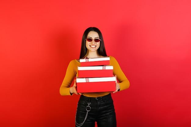 Gelukkig stijlvolle vrouw met rode zonnebril rode geschenkdozen houden en kijken naar de camera terwijl staande op rode achtergrond.