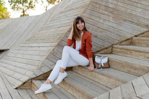Gelukkig stijlvolle vrouwelijke student poseren in modern park, wesring witte spijkerbroek, jasje en t-shirt.
