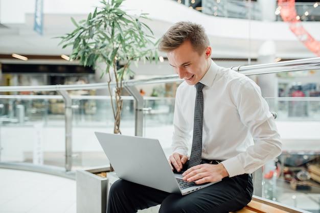 Gelukkig student chatten op internet met laptop in de hand, gekleed in een wit overhemd in business center binnen, positieve gezichtsemoties