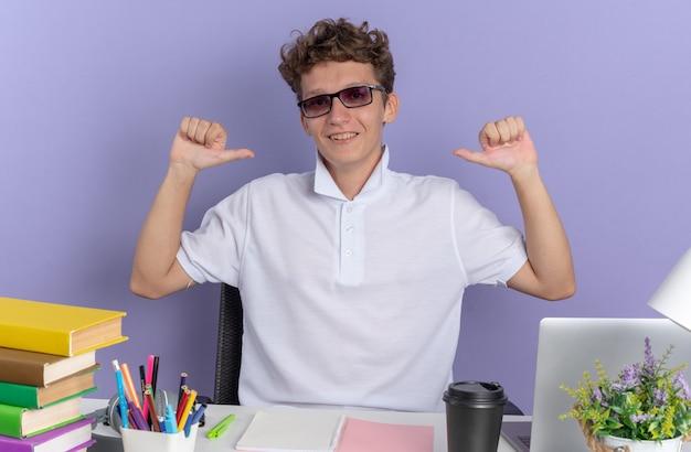Gelukkig student man in wit poloshirt met bril zittend aan de tafel met boeken glimlachend zelfverzekerd wijzend naar zichzelf over blauwe achtergrond