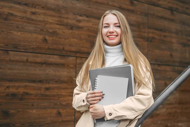 Gelukkig student meisje notebook mappen in handen te houden, glimlachend op de universiteit.