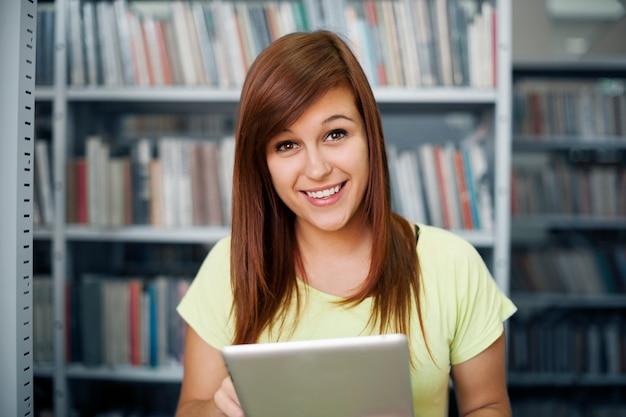 Gelukkig student met behulp van digitale tablet in bibliotheek