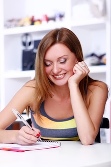 Gelukkig studentenmeisje dat somethink schrijft
