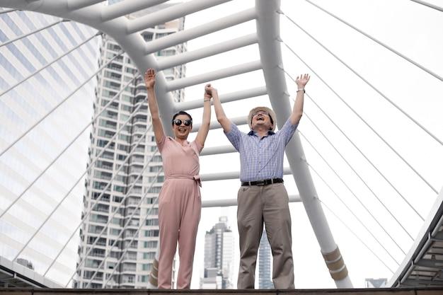 Gelukkig succes senior aziatische paren met blij op een reis samen bij landmark in thailand. senior paar reizen concept. gelukkige oom en tante staken beide handen op.