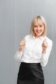 Gelukkig succesvol mooi onderneemster of studentenmeisje die duim op gebaar tonen door twee handen tegen grijze achtergrond.