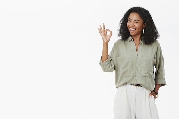 Gelukkig succesvol wijfje in een stijlvol overhemd en broek, knipogen en glimlachend opgetogen