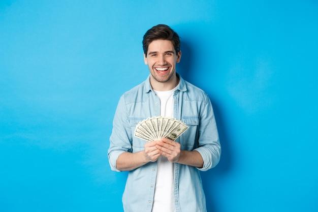 Gelukkig succesvolle man glimlachend tevreden, met geld, staande over blauwe achtergrond