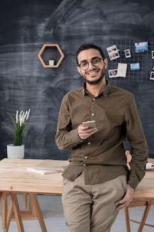 Gelukkig succesvolle mannelijke ondernemer in vrijetijdskleding die smartphone gebruikt of iemand op kantoor gaat bellen
