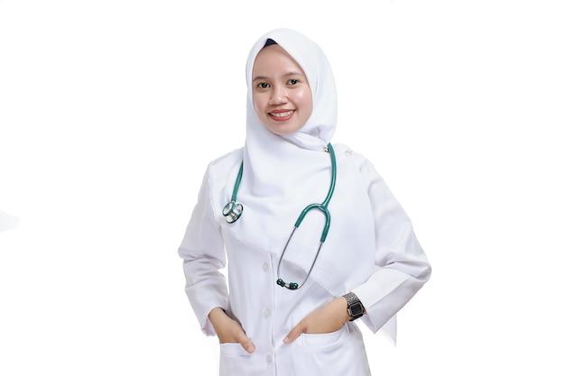 Gelukkig succesvolle vrouwelijke aziatische moslim verpleegkundige of arts, glimlachend met hand in de zak, geïsoleerd op wit