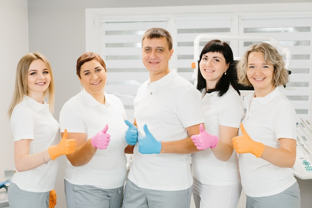 Gelukkig team die bij tandarts hun duimen in kleurenhandschoenen tegenhouden