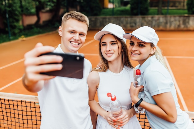 Gelukkig team na het spelen van tennis op de baan. portret van lachende jonge man en mooie vrouw met water fotograferen op telefoon.