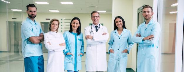 Gelukkig team van succesvolle en zelfverzekerde moderne artsen poseren en kijken op de camera naar de ziekenhuisgang