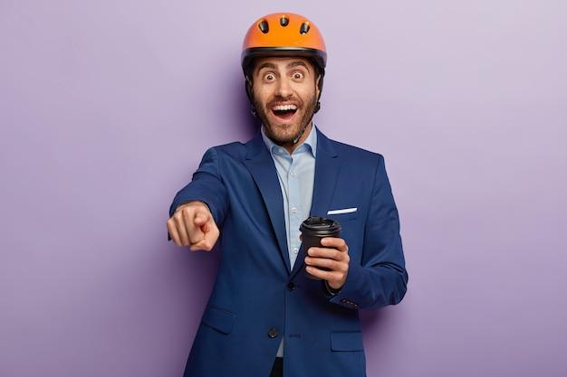 Gelukkig technicus werknemer wijst in de verte, heeft koffiepauze, draagt pak en oranje bouwhelm, wijst naar u, in hoge geest zijn