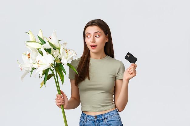 Gelukkig tedere jonge vrouw bestelde boeket bloemen levering met creditcard glimlachend tevreden en ho...