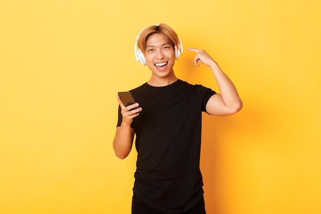 Gelukkig tevreden aziatische man houdt van muziek of podcast, wijzende vinger naar koptelefoon