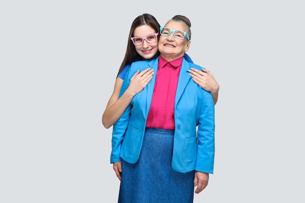 Gelukkig tevreden kleindochter knuffelen haar grootmoeder en kijken naar de camera met een brede glimlach. vriendschap of relatie en wederzijds begrip. indoor studio opname, geïsoleerd op een grijze achtergrond.