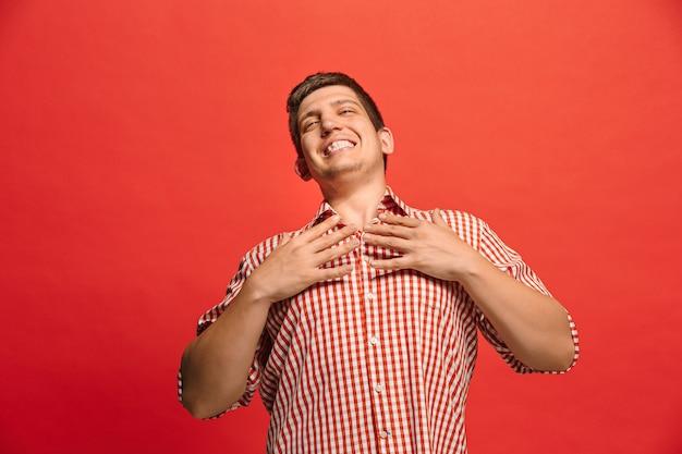 Gelukkig tevreden man permanent en glimlachend geïsoleerd op rode studio achtergrond. mooi mannelijk portret van halve lengte. jonge emotionele man